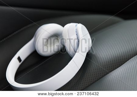 Modern Wireless Internet Technology Concept: Macro View Of The White Wireless Headphones On The Blac