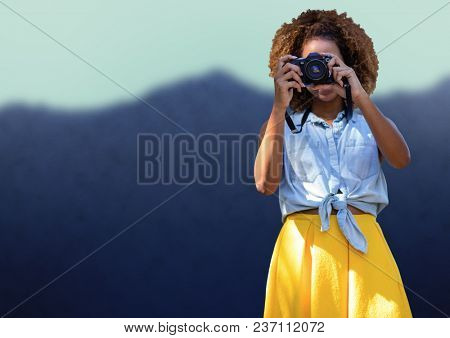 Millennial woman in summer clothes with camera against blurry mountain
