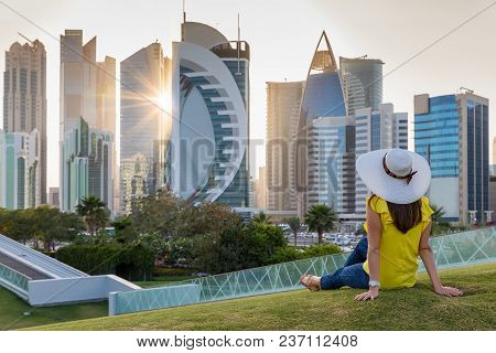 Female Tourist Sits In A Park In Front Of The Skyline Of Doha, Qatar, During Sunset Time