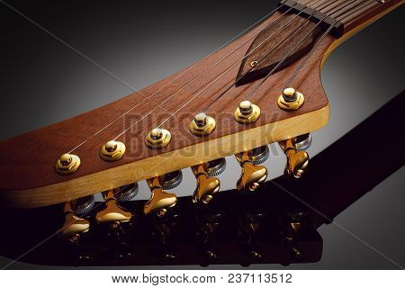 Close Up On The Headstock Of Custom Electric Guitar, Glossy Background With Reflection