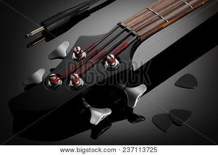 Close Up On The Black Headstock Of Electric Bass Guitar, Black Picks And Jack Cable Next To It. Glos