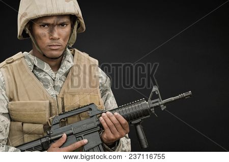 Angry soldier man holding a weapon against black background