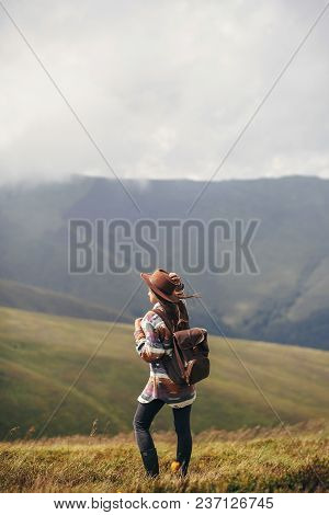 Travel And Wanderlust Concept. Traveler Hipster Girl In Hat With Backpack Exploring Misty Sunny Moun