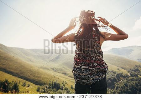 Stylish Traveler Girl In Hat With Windy Hair In Light Looking At Sunny Mountains. Summer Vacation. T