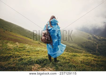 travel and wanderlust concept. traveler hipster girl in blue raincoat with backpack, exploring misty mountains. space for text. atmospheric moment.  woman walking on hills poster