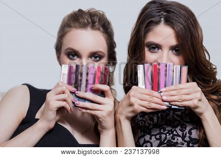 Two Beautiful Girls With Professional Make-up, Hairstyle, Holding A Lot Of Colorful Lipsticks, Lip G