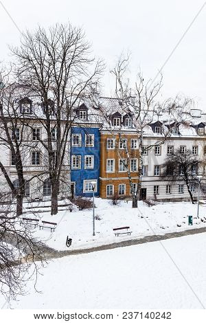 Colored Houses In Warsaw Old Town After Snow Storm In Winter, Colorful Exteriors Against The White S