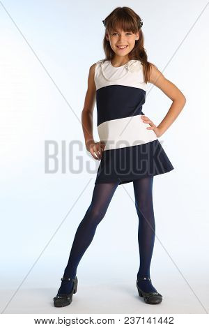 Beautiful Girl In A Striped Dress Is Standing At Full Length And Smiling. Elegant Attractive Child W