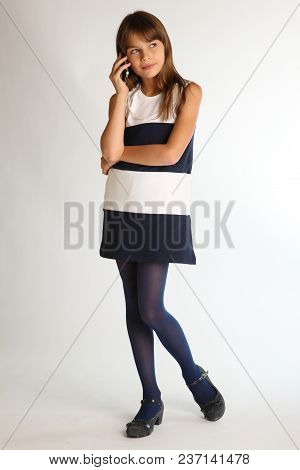 Beautiful Girl In A Striped Dress Is Standing At Full Length With A Smartphone. Elegant Attractive C