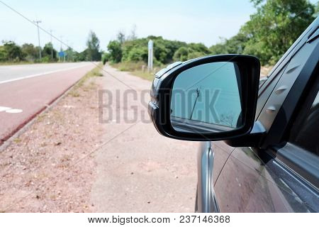 A Wing Mirror Of Black Car Parking At The Sideway In The Countryside With Asphalt Background And Tre