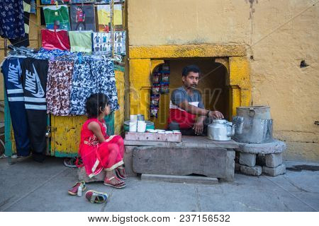 VARANASI, INDIA - MAR 17, 2018: Street seller on the banks of the sacred Ganges river selling selling milk tea - masala. According to legends, Varanasi city was founded by God Shiva about 5000 y ago.