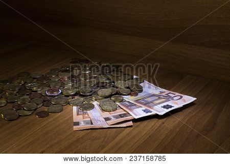 Euro And Coins On A Table Using The Light Painting Technique Composition