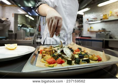 Chef is adding herbs to baked fish with vegetables