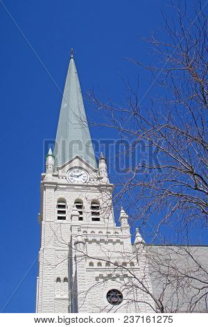 The Steeple And Clock Tower Of St. John The Evangelist Catholic Church Of Delphos, Ohio Reaches Skyw