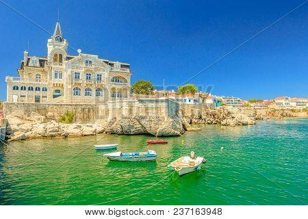 Scenic Landscape Of Abandoned Palace Seixas And Boats On The Waterfront Of Cascais, Lisbon Coast In