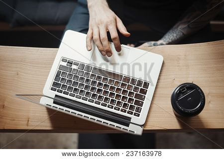 Young Man Is Working On Laptop And Drinking Coffee From Black Cup. The Black Mobile Phone Is Next To