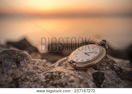 Antique Watch On A Rock In The Sunrise By The Sea