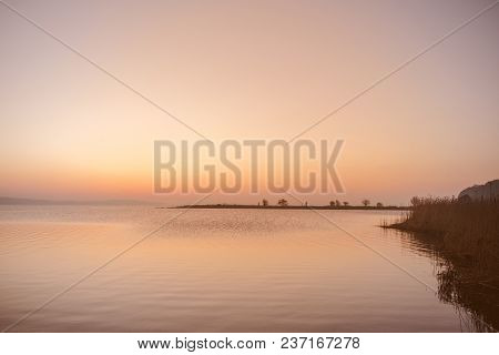 Sunrise By A Lake With Silhouettes Of Beautiful Nature With Trees And Bushes