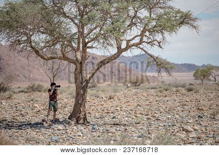 Young Male Traveler And Photographer Taking Photo Of African Animals Under The Savanna Tree In Namib