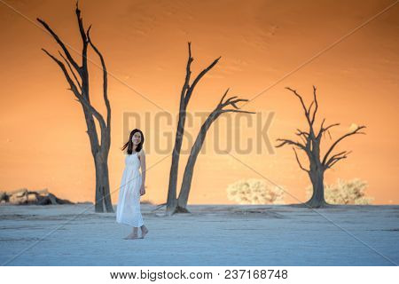 Young Beautiful Asian Girl Wearing White Dress Standing Bear Foot And Smiling In Deadvlei (sossusvle