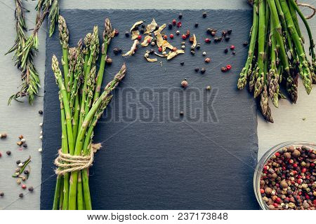 Bunches Of Asparagus With Spices On A Black Board