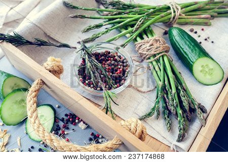 Bunches Of Asparagus With Spices And Cucumbers In A Wooden Tray