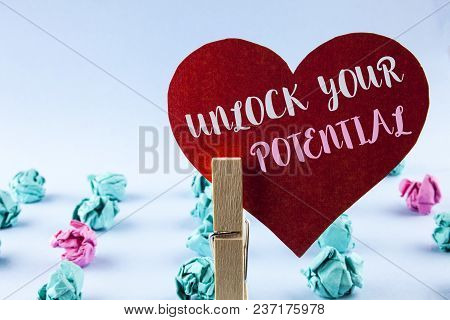 Handwriting text Unlock Your Potential. Concept meaning Reveal talent Develop abilities Show personal skills written Red Paper Heart holding by Clip plain background Paper Balls next to it. poster