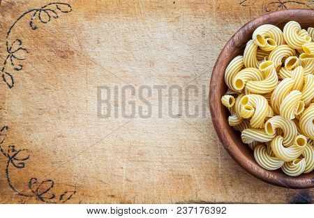 Raw Cavatappi Pasta In A Wooden Bowl On A Cutting Wooden Plaque, Texture Background With A Side. Clo