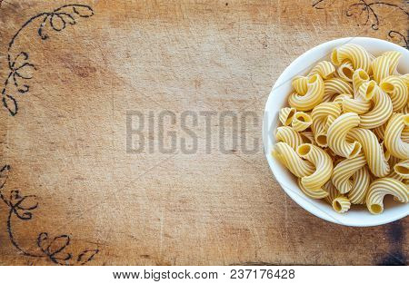 Raw Cavatappi Pasta In A White Bowl On A Cutting Wooden Plaque, Texture Background With A Side. Clos