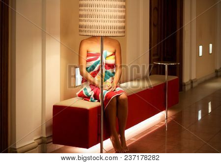 Concept: Lighting. Pretty Bold Young Woman In Bright Towel, Sitting On The Bank