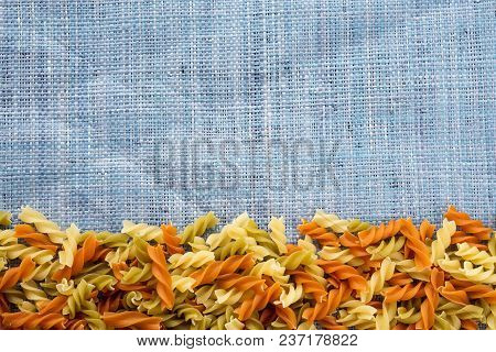 Raw Colored Spiral Beautiful Decomposed Pasta With A Bottom On A Rustic Blue Knitted Sack Texture. F