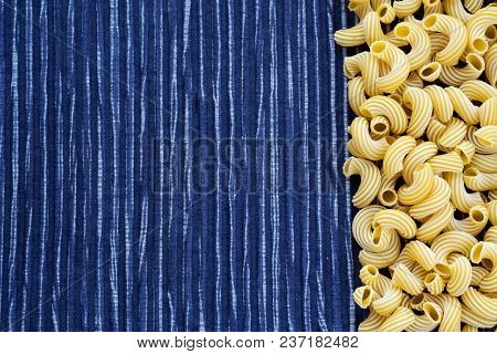 Raw Cavatappi Beautiful Decomposed Pasta With The Right, On Its Side In A Rustic Striped Blue Agains