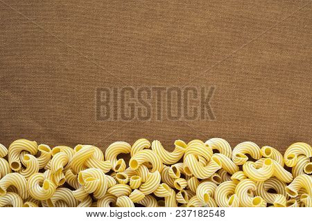 Raw Cavatappi Beautiful Decomposed Pasta From The Bottom On A Rustic Brown Textured Background. Clos