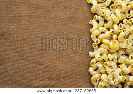 Raw Cavatappi Beautiful Decomposed Pasta With The Right, On Its Side On A Rustic Brown Textured Back