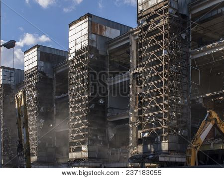 Demolition Of Old Industrial Building Whith Metal Carcass. Three Towers And Two Excavators
