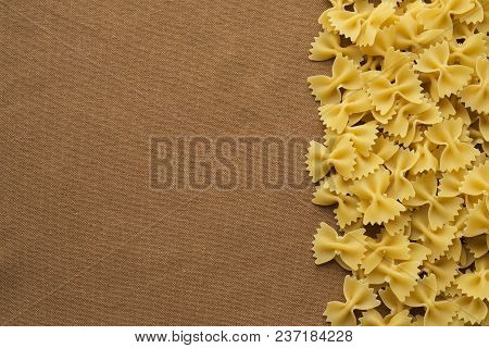 Farfalle Raw Farfallini Beautiful Decomposed Pasta With The Right, On Its Side On A Rustic Brown Tex