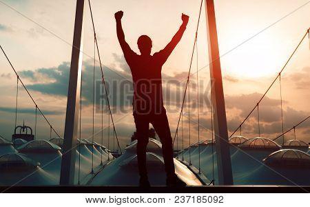 Winner Concept: Silhouette Champion Hand Holding Gold Medal Reward Against Blurred Sport Stadium Sun