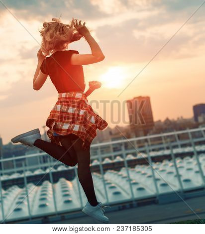 Silhouette Of Happy Joyful Woman Jumping And Having Fun In The City Against The Sunset. Freedom And