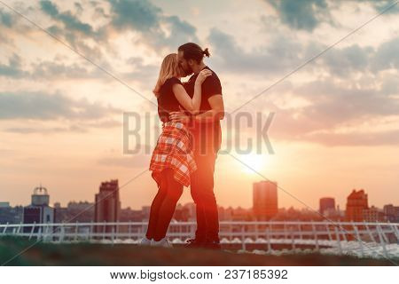 Boy And Girl Hug On The Sunset In The City. Silhouette Of Lovers In The Vanilla Sunset.