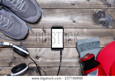 Top View Of Sport Shoes, Sound Headphone, Smartphone, Hat, Towel And Water Bottle Photographed On An