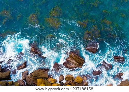 Top Aerial View Of Blue Waves Crashing On Rocky Australian Coastline. Summer Seascape With Ocean Wav