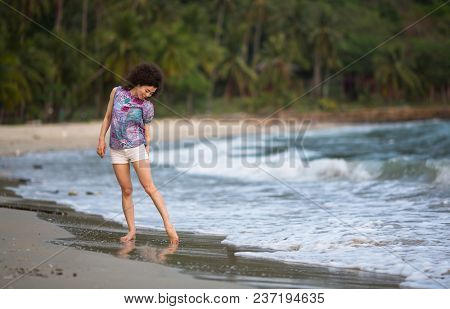 Young mixed race woman walking on the sea beach.