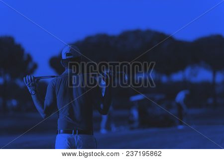 golfer  from back looking to ball and  hole in distance, handsome middle eastern golf player portrait from back with beautiful sunset in background duo tone