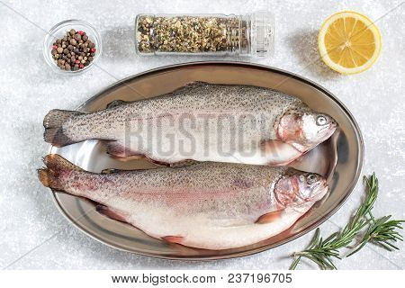 Two Fresh Trout On Metal Tray And Ingredients For Cooking (pepper, Salt, Lemon, Seasoning And Rosema