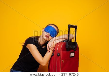 A Young Girl Is Sleeping On A Large Suitcase, In Front Of A Mask To Sleep, Waiting For Her Plane, A