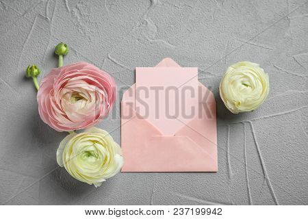 Beautiful Ranunculus Flowers With Envelope On Grey Background