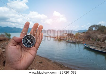 Left Hand Holding The Magnetic Compass Shows The Directions North, South, East, And West On The Comp