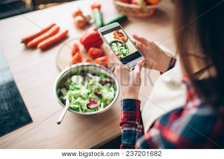 Woman makes photo of vegetable salad cooking