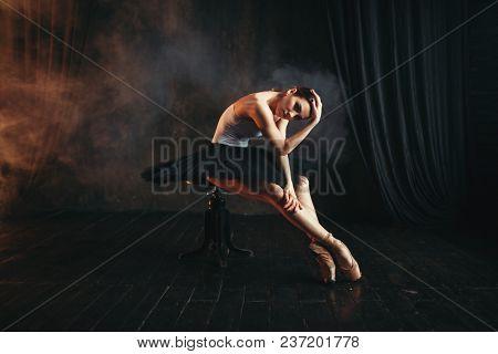 Ballerina sitting on black banquette in theatre