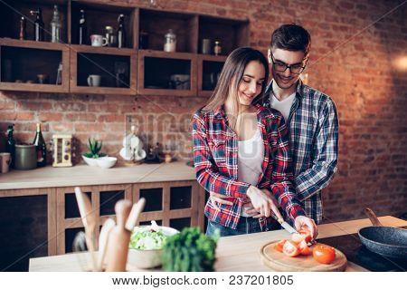 Husband hugs wife while she cooking fresh salad